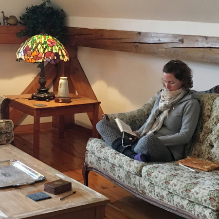 Student on couch reading on weekend retreat