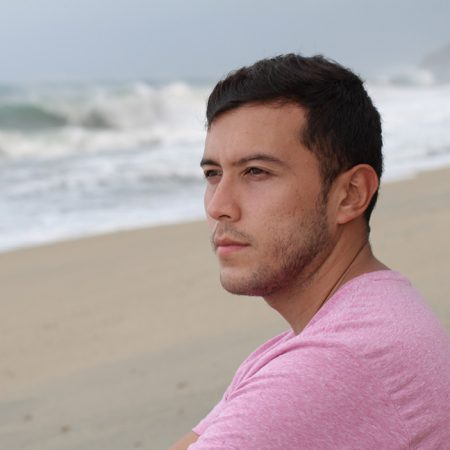 Young man on beach, looking pensive